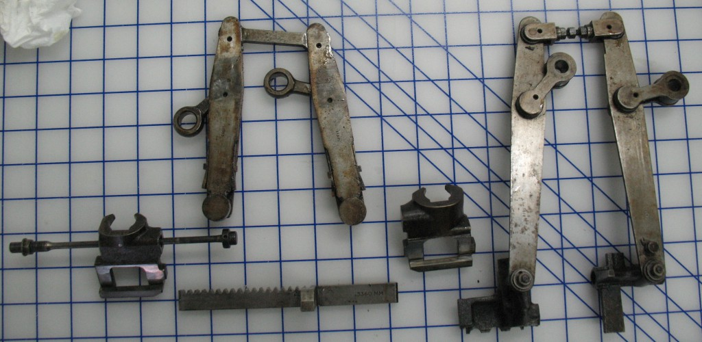 These are the parts I had to remove before I could lift the pin block cover: On the right, the pin jaws still attached to their tongs, and on the left, the rack, matrix jaws, and matrix jaw tongs.