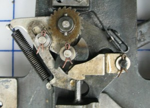As the drive arm descends, the pawl moves clockwise around the ratchet wheel.