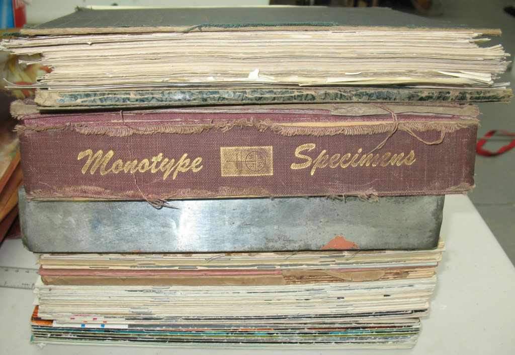 Two or three specimen books, plus a stack of periodicals.
