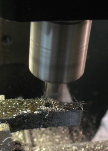 "A regular (finishing) ⅜″ endmill is cutting the final pass of the outside contour. This ""final"" pass was run a second time offset a bit because the mill turned out to be slightly under its nominal diameter, leaving the part too wide."