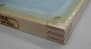 This shows the finger-jointed corner of the frame and the staple-and-glue attachment of the screening