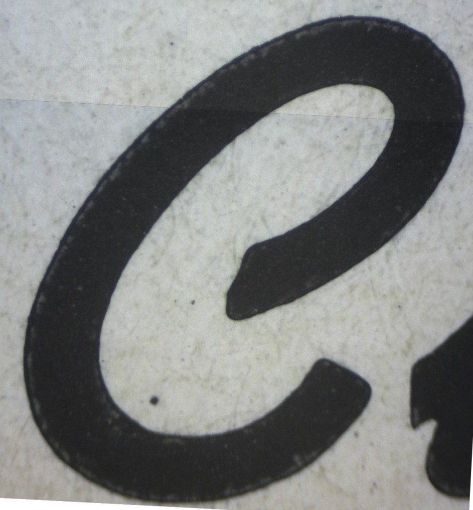 A magnified image of the C. The ink gain is actually visible because the edge of the type is marked by a faint lighter line. All the black area beyond that is the ink gain.