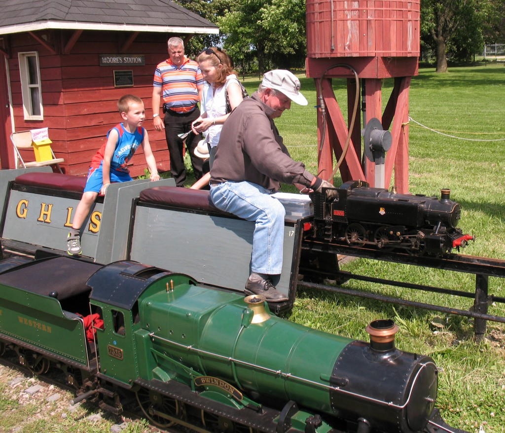 Loading a few more chips of coal into the firebox. The train in the foreground is powered by a hidden gasoline engine, perhaps stolen off a weed trimmer.